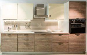 Линейная бело-древесная кухня с дизайнерскими ручками 1