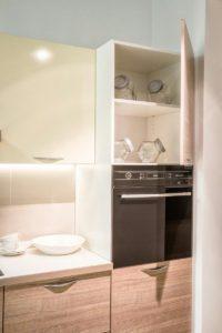 Линейная бело-древесная кухня с дизайнерскими ручками 5